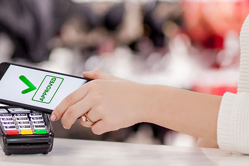 POS terminal, Payment Machine with mobile phone on store background. Contactless payment with NFC technology 1142622410