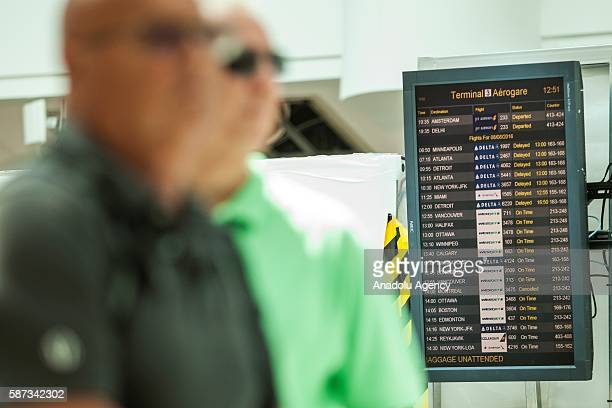 A terminal sign board is seen with delay messages as passengers in line await updates from Delta airline employees at Pearson International airport...