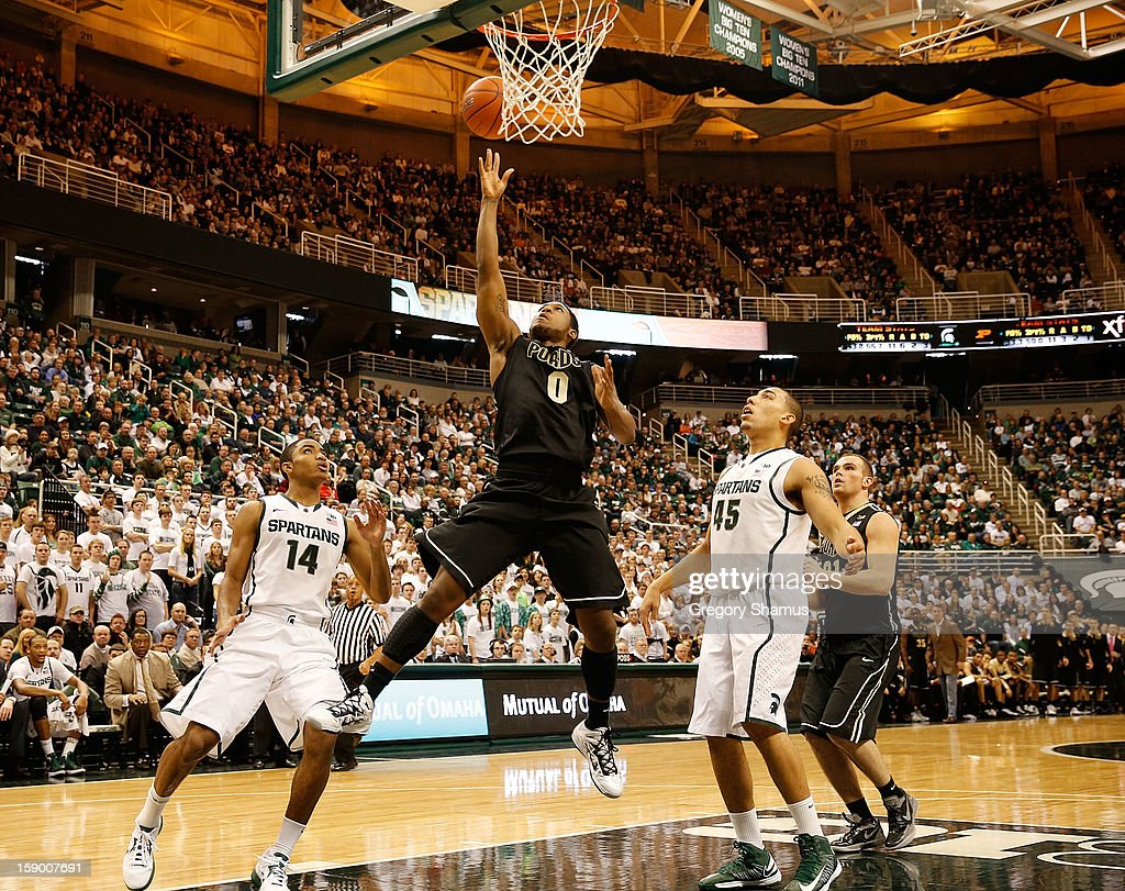 Terone Johnson #0 of the Purdue Boilermakers gets to the basket between Gary Harris #14 and Denzel Valentine #45 of the Michigan State Spartans at the Jack T. Breslin Student Events Center on January 5, 2013 in East Lansing, Michigan. Michigan State won the game 84-61.
