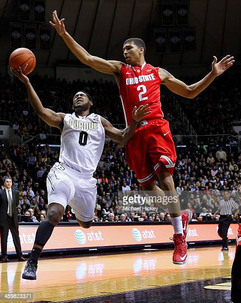 Terone Johnson of the Purdue Boilermakers takes the ball to the hoop as Marc Loving of the Ohio State Buckeyes defends at Mackey Arena on December 31...