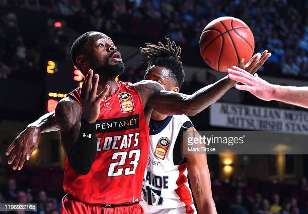 Terrace White of the Wildcats juggles a rebound in front of Eric Griffin of the 36ers during the round 13 NBL match between the Adelaide 36ers and...
