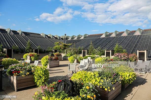 Terrasse mit Stühlen und Blumen auf dem Dach des Gebäudes