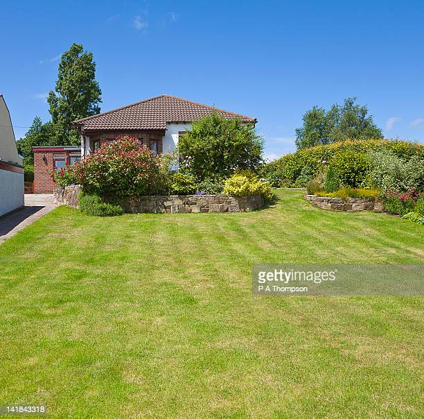 terraced border of shrubs in large garden and bungalow pr - lawn stock pictures, royalty-free photos & images