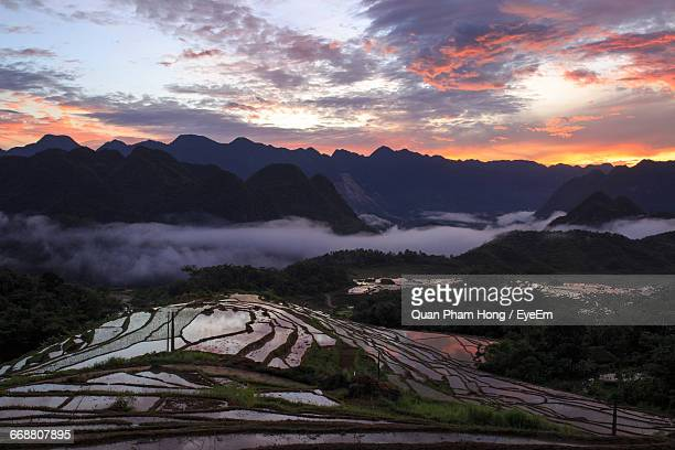 terraced field by mountains against cloudy sky during sunrise - hong quan stock pictures, royalty-free photos & images