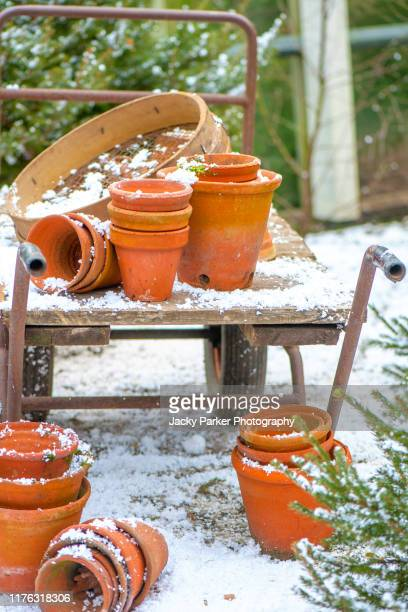 terracotta orange garden flower pots/containers and a garden sieve on a trolley in the winter snow - horticulture stock pictures, royalty-free photos & images