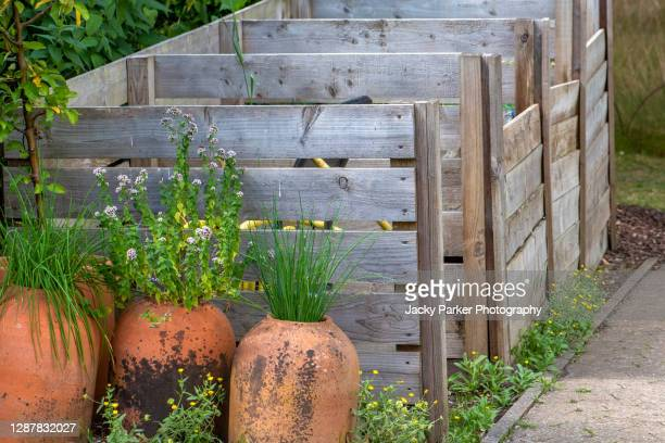 terracotta pots beside wooden/pallet compost bins for composting - pallet industrial equipment stock pictures, royalty-free photos & images
