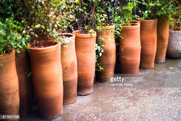 terracotta pots in a line in the rain - lyn holly coorg stock pictures, royalty-free photos & images
