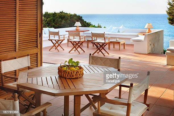 Terracotta terrace with wooden furniture of a beautiful seaside house