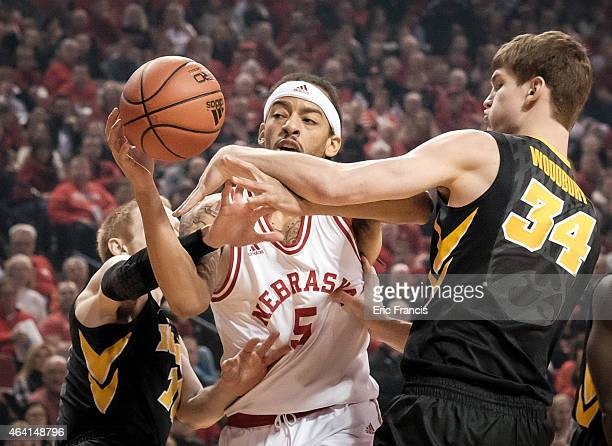 Terran Petteway of the Nebraska Cornhuskers is fouled by Adam Woodbury and Mike Gesell of the Iowa Hawkeyes during their game at Pinnacle Bank Arena...
