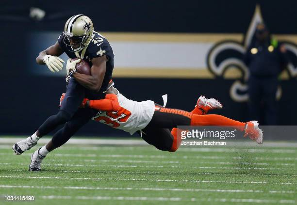 Terrance Mitchell of the Cleveland Browns tackles Michael Thomas of the New Orleans Saints during the second quarter at MercedesBenz Superdome on...