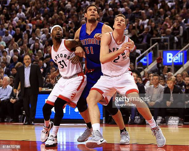 Terrance Ross Jakob Poeltl of the Toronto Raptors and Boban Marjanovic of the Detroit Pistons watch for a rebound during the first half of an NBA...