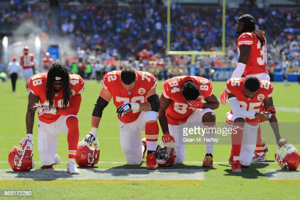 Terrance Smith, Eric Fisher, Demetrius Harris, and Cameron Erving of the Kansas City Chiefs is seen taking a knee before the game against the Los...