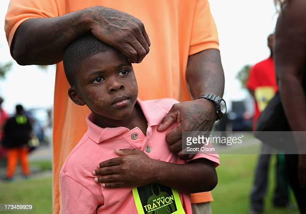 Terrance Smith II stands with his father during a protest against the George Zimmerman verdict at Mellon Park on July 14 2013 in Sanford Florida...