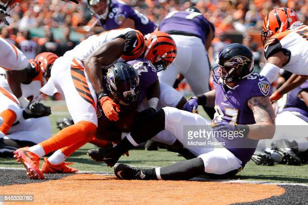 Terrance West of the Baltimore Ravens runs through George Iloka of the Cincinnati Bengals to score a touchdown during the second quarter at Paul...