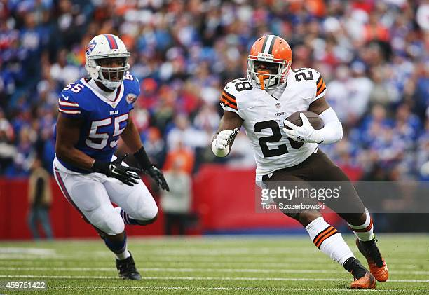 Terrance West of the Cleveland Browns is chased down by Jerry Hughes of the Buffalo Bills during the first half at Ralph Wilson Stadium on November...