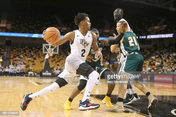 Terrell Allen of the UCF Knights dribbles to the net against Jabbar Singleton and Jordan Capps of the Southeastern Louisiana Lions during a NCAA...