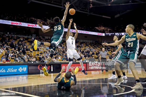 Terrell Allen of the UCF Knights scores a basket as James Currington and Marlain Veal of the Southeastern Louisiana Lions defend during a NCAA...