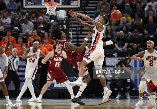 Terrell Brown of the New Mexico State Aggies battles for the ball with J'Von McCormick of the Auburn Tigers during the first half in the first round...