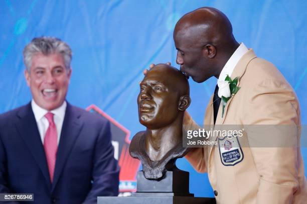 Terrell Davis kisses his bust as presenter Neil Schwartz looks on during the Pro Football Hall of Fame Enshrinement Ceremony at Tom Benson Hall of...