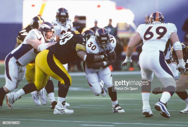 Terrell Davis of the Denver Broncos gets tackled by Joel Steed of the Pittsburgh Steelers during an NFL football game circa 1997 at Three Rivers...