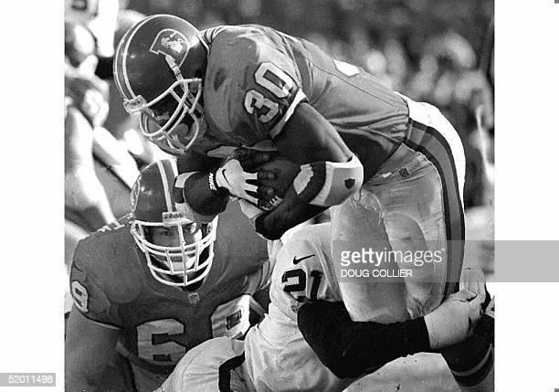 Terrell Davis of the Denver Broncos scores a touchdown past Oakland Raiders defender Darren Carrington as Denver's Mark Schlereth looks on during...