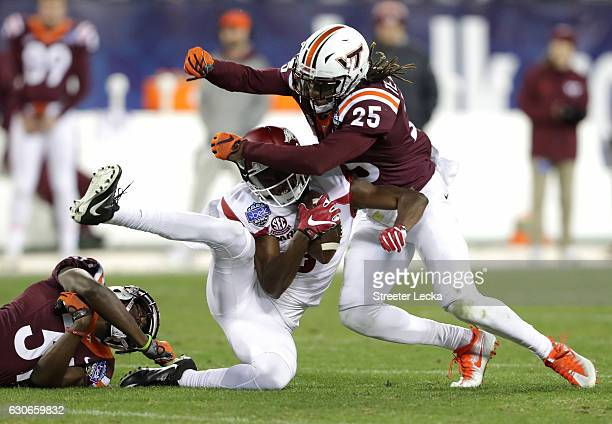 Terrell Edmunds of the Virginia Tech Hokies hits Dominique Reed of the Arkansas Razorbacks during the Belk Bowl at Bank of America Stadium on...