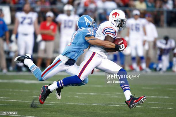 Terrell Owens of the Buffalo Billls runs with the football after catching a pass in front of Cortland Finnegan of the Tennessee Titans during the Pro...