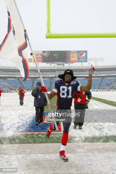 Terrell Owens of the Buffalo Bills runs off the field with a Bills flag after the Bills defeated the Indianapolis Colts at Ralph Wilson Stadium on...