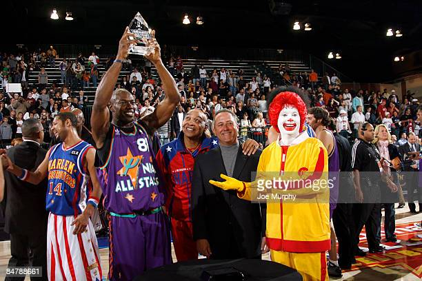 Terrell Owens of the Dallas Cowboys poses with his MVP trophy and McDonald's executives during the McDonald's AllStar Celebrity Game on center court...