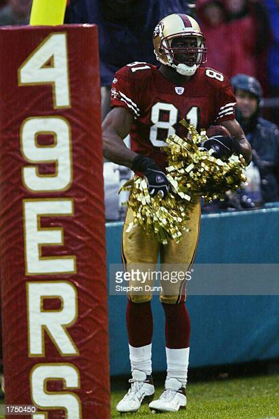 Terrell Owens of the San Francisco 49ers uses the cherrleaders' pom poms to celebrate his touchdown catch during the game against the Green Bay...