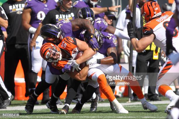Terrell Suggs and Brandon Carr of the Baltimore Ravens combine to tackle Tyler Eifert of the Cincinnati Bengals during the fourth quarter at Paul...