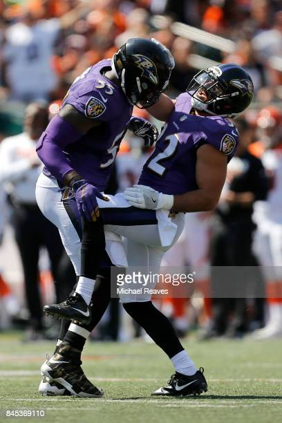 Terrell Suggs of the Baltimore Ravens is congratulated by Eric Weddle of the Baltimore Ravens after causing a fumble during the third quarter of the...