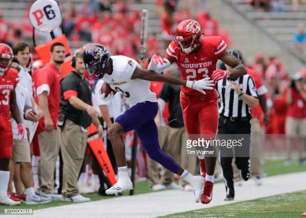 Terrell Williams of the Houston Cougars forces Tahj Deans of the East Carolina Pirates out of bounds in the third quarter at TDECU Stadium on...