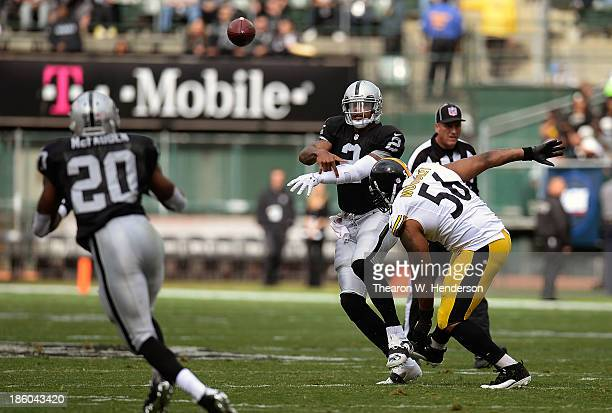 Terrelle Pryor of the Oakland Raiders gets his pass off to Darren McFadden while being pursued by LaMarr Woodley of the Pittsburgh Steelers during...