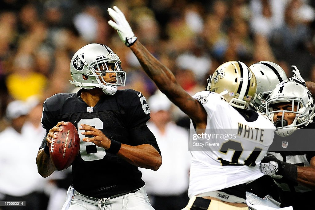 Terrelle Pryor #6 of the Oakland Raiders is pressured by Corey White #24 of the New Orleans Saints during a preseason game at the Mercedes-Benz Superdome on August 16, 2013 in New Orleans, Louisiana.