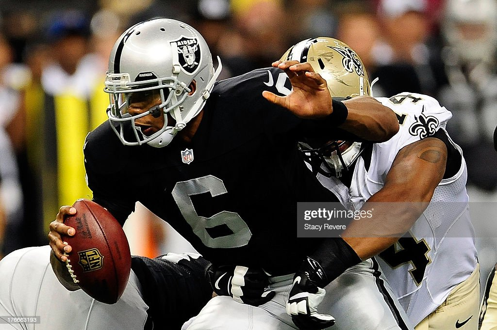 Terrelle Pryor #6 of the Oakland Raiders is sacked by Glenn Foster #74 of the New Orleans Saints during a preseason game at the Mercedes-Benz Superdome on August 16, 2013 in New Orleans, Louisiana. The Saints won 28-20.