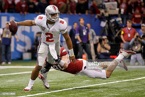 Terrelle Pryor of the Ohio State Buckeyes looks to avoid the sack attempt by Jake Bequette of the Arkansas Razorbacks in the second half during the...