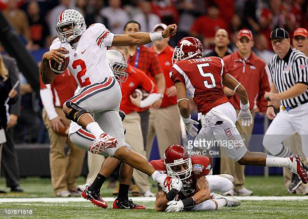 Terrelle Pryor of the Ohio State Buckeyes runs with the football as he avoids a tackle by Isaac Madison of the Arkansas Razorbacks in the first...