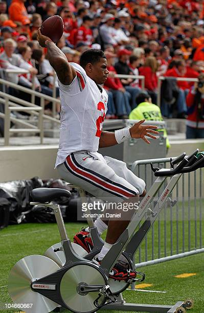 Terrelle Pryor of the Ohio State Buckeyes throws a football while riding an exercise bicycle on the sidelines after suffering a leg injury against...