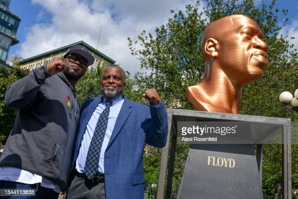 """Terrence Floyd, and New York City Deputy Mayor, Phillip Thompson, raise their fists in front of the """"Floyd"""" sculpture during Confront Art's First..."""