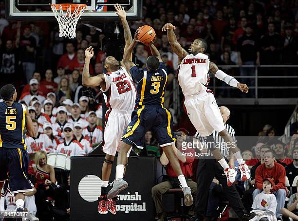 Terrence Jennings and Terrence Williams of the Louisville Cardinals block the shot of Devin Ebanks of the West Virginia Mountaineers during the Big...
