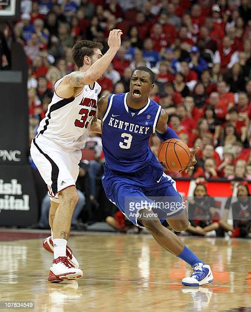 Terrence Jones of the Kentucky Wildcats dribbles the ball while defended by Mike Marra of the Louisville Cardinals during the game at the KFC Yum...