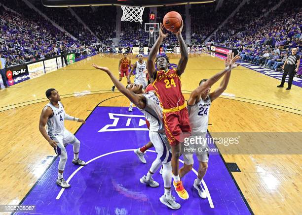 Terrence Lewis of the Iowa State Cyclones drives to the basket between Levi Stockard III and Pierson McAtee of the Kansas State Wildcats during the...
