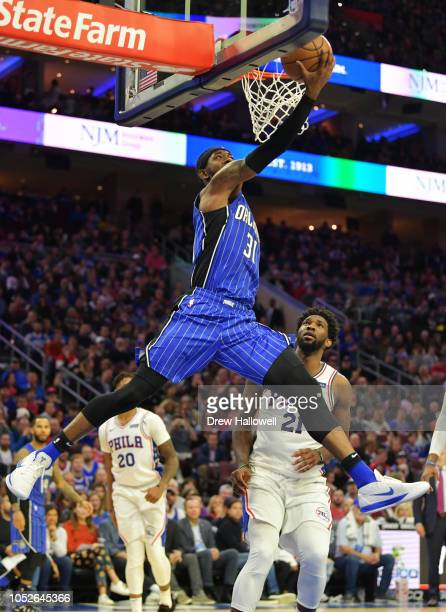 Terrence Ross of the Orlando Magic lays up a shot as Joel Embiid of the Philadelphia 76ers watches at Wells Fargo Center on October 20 2018 in...