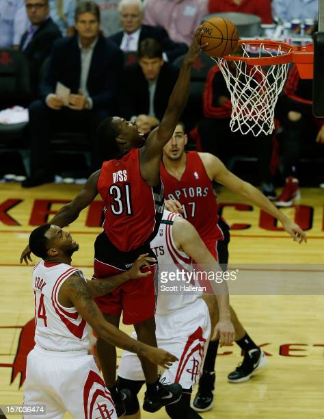 Terrence Ross of the Toronto Raptors dunks over Omer Asik and Daequan Cook of the Houston Rockets at the Toyota Center on November 27, 2012 in...