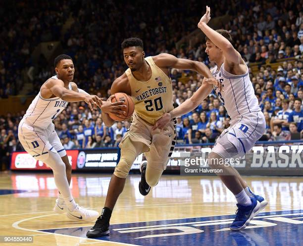 Terrence Thompson of the Wake Forest Demon Deacons drives between Trevon Duval and Grayson Allen of the Duke Blue Devils during their game at Cameron...