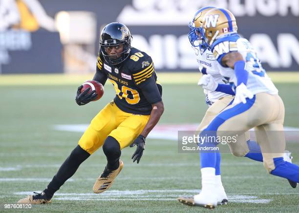 Terrence Toliver of the Hamilton TigerCats runs with the ball against the Winnipeg Blue Bombers in a CFL game at Tim Hortons Field on June 29 2018 in...