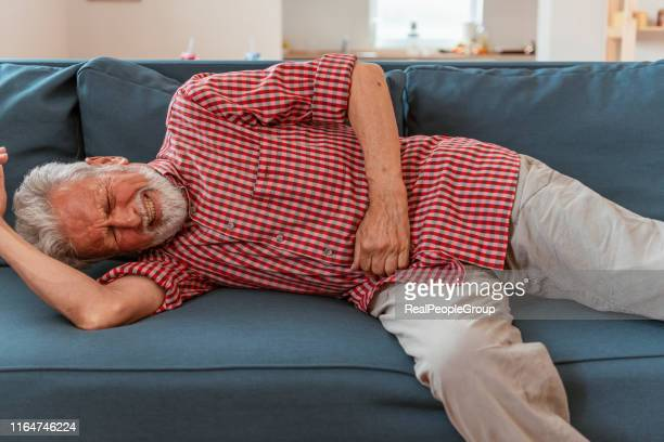 terrible stomachache. sick senior man suffering from stomach ache holding his stomach in bedroom - flat stomach stock pictures, royalty-free photos & images