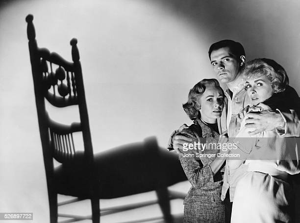 Terrified Lila Crane and Marion Crane stand in the arms of Sam Loomis in a publicity still for Alfred Hitchcock's Psycho.