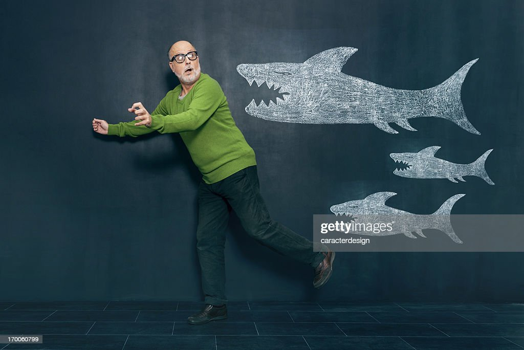 Terrified man escaping from sharks : Stock Photo